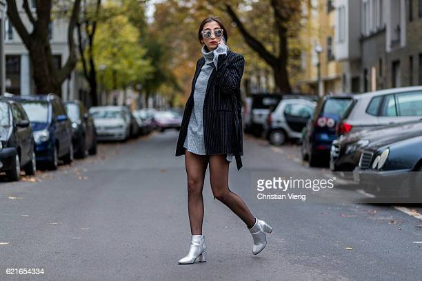 Nadja Ali talking on her phone wearing a black white stripped blazer from Edited a grey turtleneck sweater with long sleeves from Edited Falke tights...