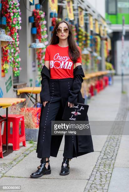 Nadja Ali wearing a black Lala Berlin coat, a red Ganni tshirt with the print Cherry bomb, black Zara pants, Gucci clutch with the print blind for...