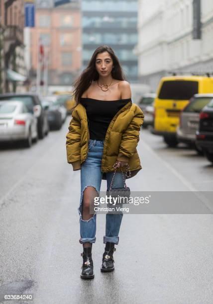 Nadja Ali wearing a black off shoulder Brandy Mellville shirt a Sabrina Dehoff necklace ripped Levis denim jeans net tights Wolford a mustard down...