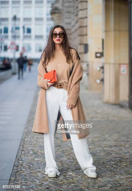 Nadja Ali wearing beige Drykorn wool coat beige Uniqlo sweater white Mango pants Fendi sunglasses orange Chanel bag Gucci belt Chanel necklace on...