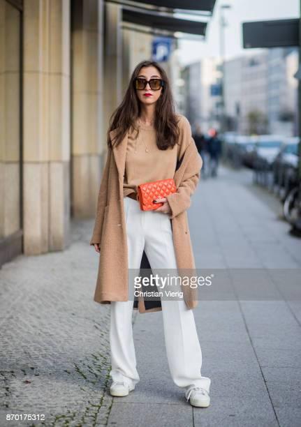 Nadja Ali wearing beige Drykorn wool coat beige Uniqlo sweater white Mango pants Fendi sunglasses orange Chanel bag Gucci belt Chanel necklace on...
