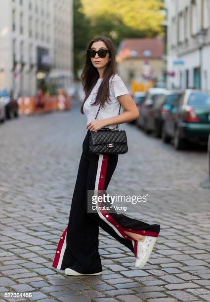 Nadja Ali wearing black Zara pants with buttons and slit black Chanel bag white tshirt Brandy Mellville white Saint Laurent sneakers Celine...