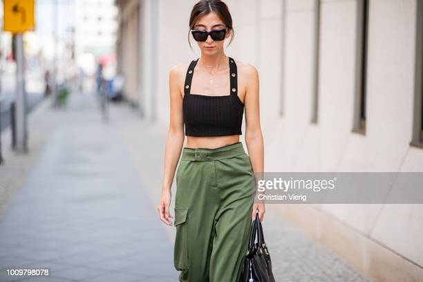Nadja Ali wearing olive green military pants Lala Berlin cropped Topshop top Balenciaga boots Prada bag on August 2 2018 in Berlin Germany