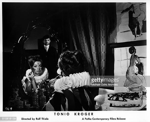 Nadja Tiller applies clown make up on as JeanClaude Brialy as Tonio Kroeger look on in a scene from the movie Tonio Kroeger circa 1964
