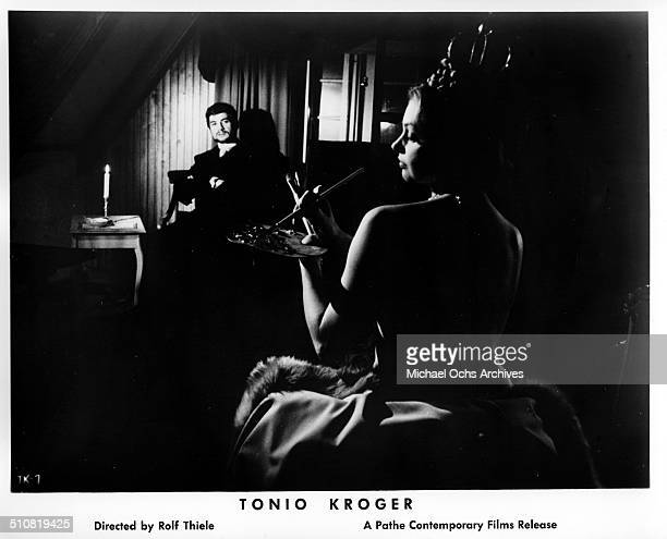 Nadja Tiller paints as JeanClaude Brialy as Tonio Kroeger looks on in a scene from the movie Tonio Kroeger circa 1964