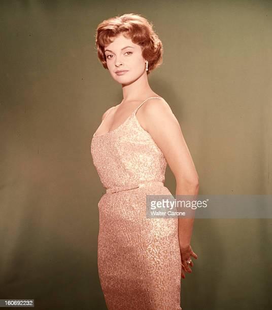 Nadja Tiller Portrait en studio de l'actrice Nadja TILLER debout les mains jointes dans le dos sur fond vert vêtue d'une robe brodée de teinte nacrée...