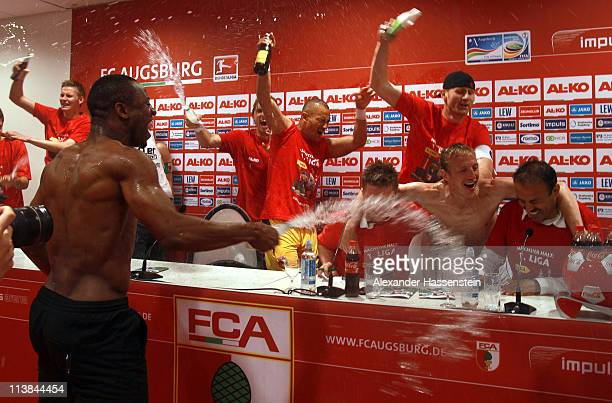 Nado Rafael of Augsburg and his team mates celebrates pours water over her head coach Jos Luhukay during a press conference after the Second...