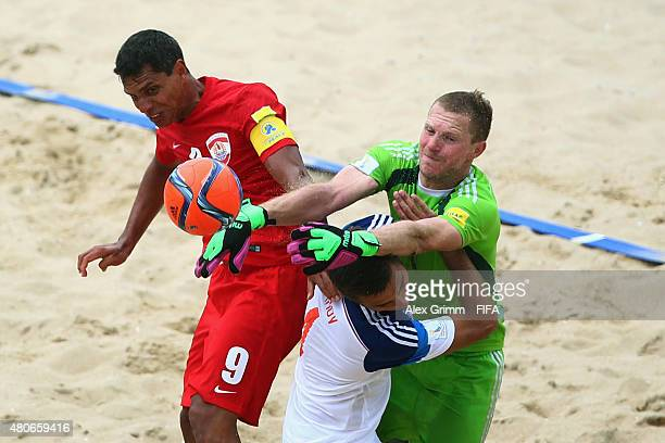 Naea Bennett of Tahiti is challenged by Alexey Makarov and goalkeeper Andrey Bukhlitskiy of Russia during the FIFA Beach Soccer World Cup Portugal...