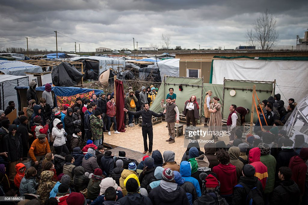 Naeem Hayat (C) playing Hamlet from Shakespeare's Globe performs performs to migrants at the Good Chance Theatre Tent in the Jungle Refugee Camp on February3, 2016 in Calais, France. The Globe to Globe tour is aiming to perform Hamlet in every country on earth over two years. They began on the 450th anniversary of Shakespeare's birth 23 April 2014, have performed in 166 countries to date and will finish at the Globe Theatre in London on the 400th anniversary of his death 23 April 2016.
