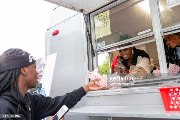Nafessa Williams and Naomie Harris are seen serving from a food truck during the Black Blue cast members' visit to Morehouse College on October 24...