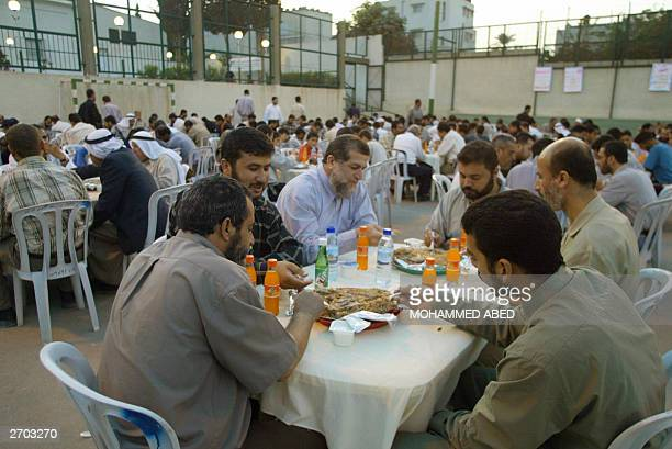 Nafez Azam a senior member of the Palestinian Islamic Jihad movement eats with families of Palestinian martyrs of the IsareliPalestinian conflict at...