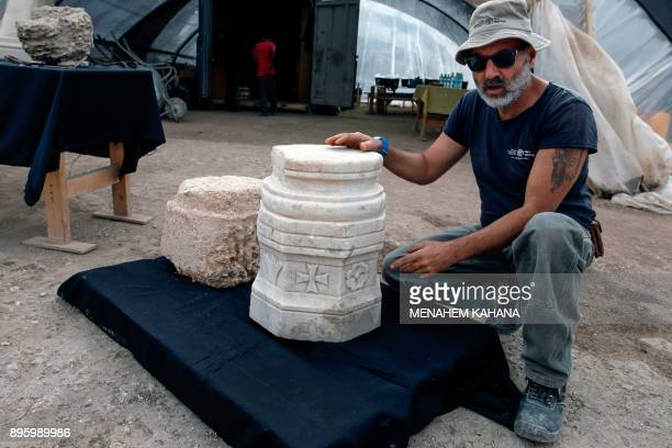 Naftali Aizik an archaeologist of the Israel Antiquities Authority shows a marble pillar base with a cross found during the excavation of a...