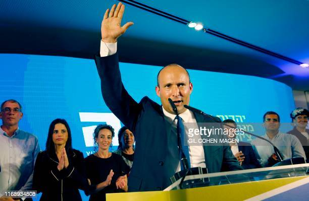 Naftali Bennett member and candidate for the New Right party that is part of the Yamina political alliance speaks while flanked by party leader...