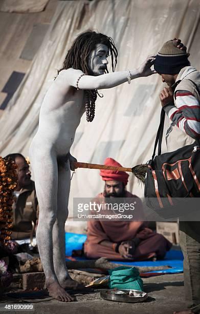 Naga sadhu applying tilak on the forehead of a pilgrim at Maha Kumbh Allahabad Uttar Pradesh India