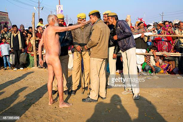 Naga sadhu discusses a point with some policemen during maha Kumbh mela. Kumbh Mela is a site of mass pilgrimage in which Hindus gather at a sacred...