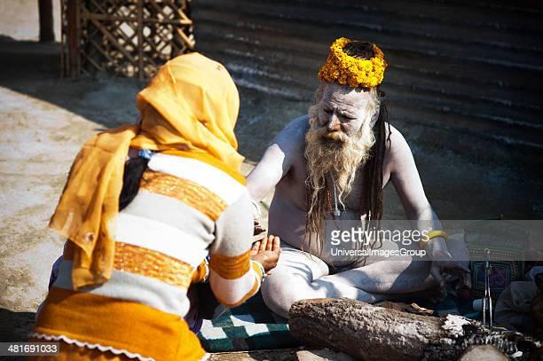 Naga Sadhu giving prasad to a woman at Maha Kumbh Allahabad Uttar Pradesh India