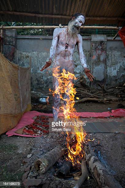 Naga sadhu in Gangasagar transit camp in Kolkata is warming up by burning wood to adjust with the cold winter morning