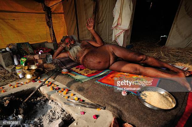 Naga Sadhu lies down in his tent at the Sangam the confluence of Ganges Yamuna and mythical Saraswati rivers during Maha Kumbh Mela
