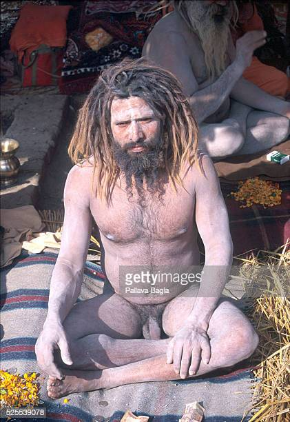 Naga Sadhu or naked holy man sitting in the crossed legged pose