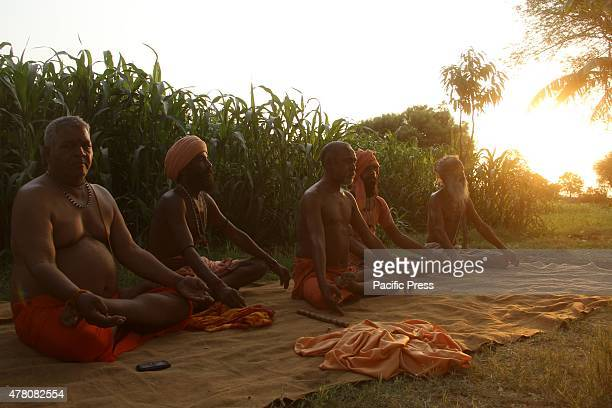 Naga Sadhu perform yoga to the villagers on first world yoga day at Dhaulpur Naga Sadhus are a particular group of Shaivite saints who reside in the...