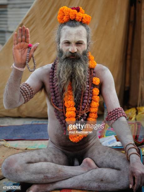 Naga Sadhu poses for a photograph at the Sangam the confluence of Ganges Yamuna and mythical Saraswati rivers during Maha Kumbh Mela