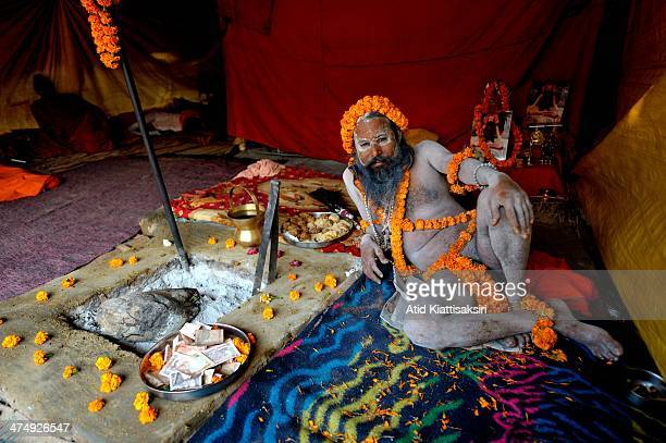 Naga Sadhu relaxes in his tent at the Kumbh Mela grounds at the Sangam or confluence of Yamuna, Ganges and mythical Saraswati rivers.