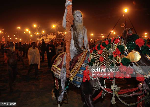 Naga Sadhu rides a horse to the Sangam the confluence of the holy rivers Ganges Yamuna and the mythical Saraswati for the Shahi Snan of Mauni...