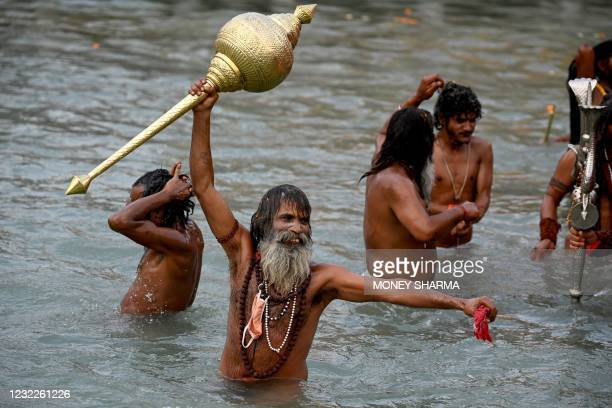 Naga Sadhu takes a holy dip in the waters of the Ganges River on the day of Shahi Snan during the ongoing religious Kumbh Mela festival, in Haridwar...