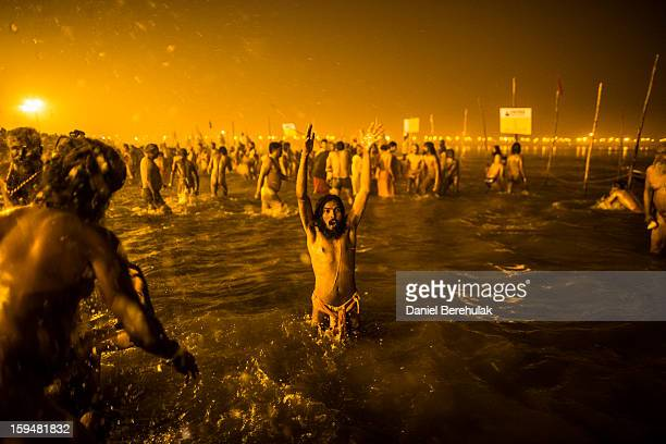 Naga sadhus bathe in the waters of the holy Ganges river during the auspicious royal bathing day of Makar Sankranti the start of the Maha Kumbh Mela...