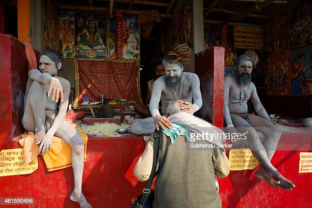 Naga sadhus bless pilgrims at Gangasagar Island due to shortage of temporaryt tents Every year thousands of Hindu pilgrims from all over India flock...