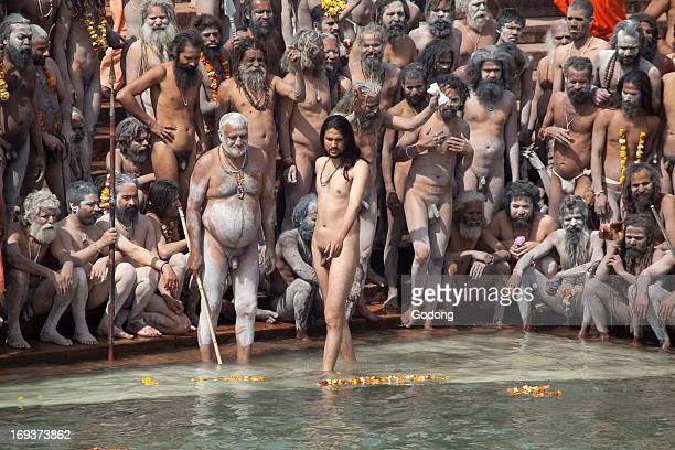 Naga sadhus on HarkiPauri ghat about to take a dip in the river Ganges on the occasion of 'Somvati Amavasya' a no moon day in the traditional Hindu...