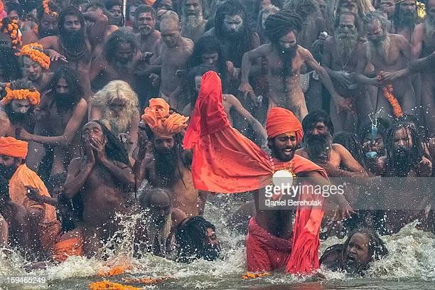 Naga sadhus run in to bathe in the waters of the holy Ganges river during the auspicious bathing day of Makar Sankranti of the Maha Kumbh Mela on...