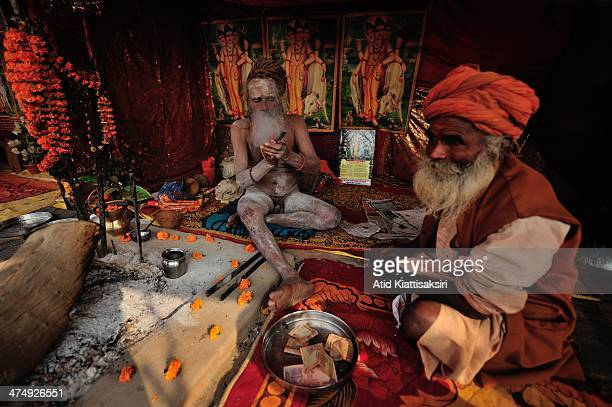 Naga Sadhus smokes a Chillum in his tent on the grounds of the Maha Kumbh Mela