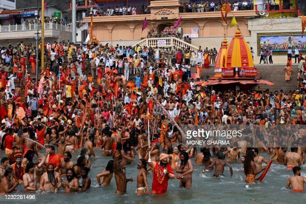 Naga Sadhus take a holy dip in the waters of the Ganges River on the day of Shahi Snan during the ongoing religious Kumbh Mela festival, in Haridwar...