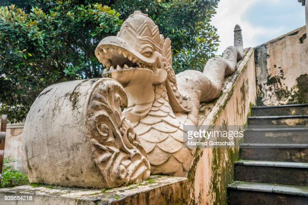 naga sculpture at the staircase of the gate to the taman sari water castle, yogyakarta - kraton stock pictures, royalty-free photos & images