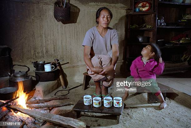 Naga woman named Kono prays with her daughter after preparing a traditional meal over a wood fire in her home The Naga people are known by their...