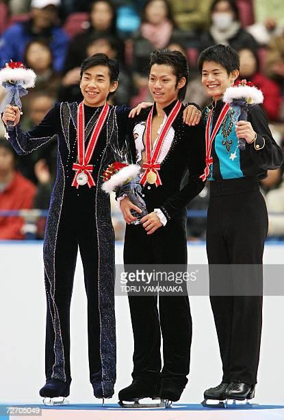 Japanese skater Daisuke Takahashi shares a light moment with his compatriots second-placed Nabunari Oda and third-placed Takahiko Kozuka on the...