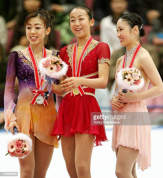 Japanese skater Mao Asada shares a light moment with her compatriot second-placed Fumie Suguri and third-placed Yukari Nakano during an awarding...