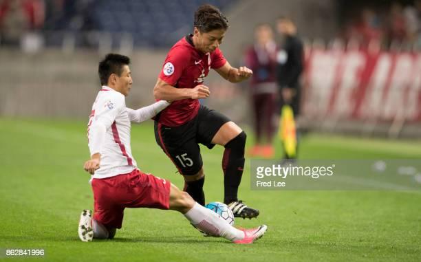 Nagasawa Kazuki of Urawa Red Diamonds controls the ball Wu Lei of Shanghai SIPG during the AFC Champions League semi final second leg match between...