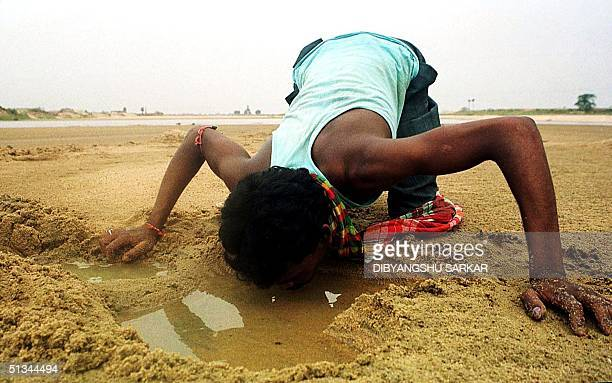 Nagendra a labourer in a closeby construction site quenches his thirst from a waterhole dug at a driedup river bed at Birbhum in the eastern Indian...