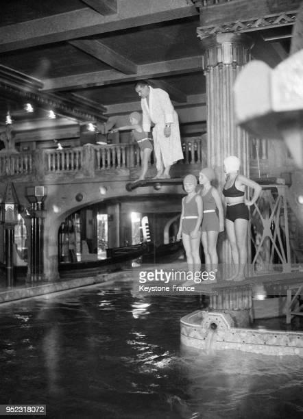Nageuses sur le plongeon de la piscine du cabaret Lido à Paris France en 1932