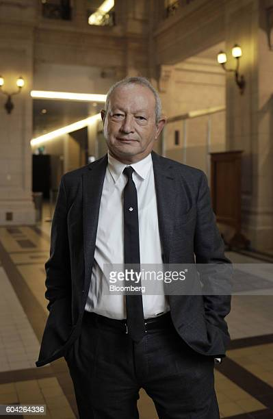 Naguib Sawiris chairman and chief executive officer of Orascom Telecom Media And Technology Holding SAE stabnds for a photograph after a Bloomberg...
