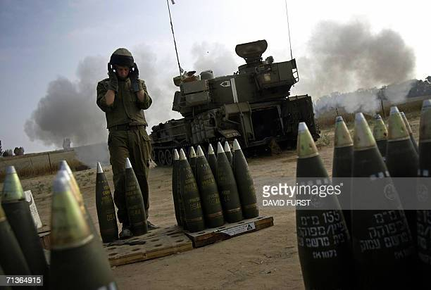 An Israeli soldier covers his ears as a mobile artillery unit fires a 155 mm round at the northern Gaza Strip from a stretch of farmland located near...
