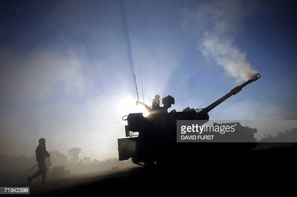 An Israeli soldier rushes to deliver a fresh 155 mm artillery shell to a mobile artillery unit as it fires at the Gaza Strip from a stretch of...