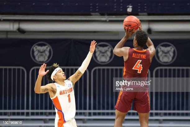 Nahiem Alleyne of the Virginia Tech Hokies shoots a 3-point basket against Tre Mann of the Florida Gators to tie the game in the second half in the...