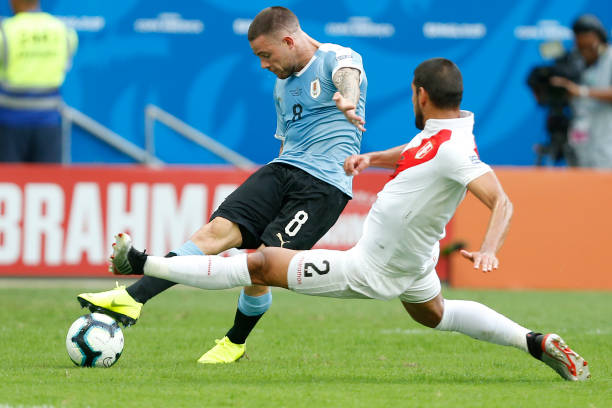 Nahitan Nandez of Uruguay kicks the ball under pressure of Luis Abram of Peru during the Copa America Brazil 2019 quarterfinal match between Uruguay...