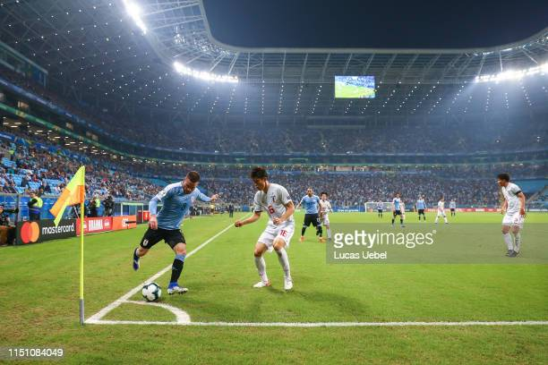 Nahitan Nández of Uruguay battles for the ball against Takehiro Tomiyasu of Japan during the Group C match between Uruguay and Japan during Copa...
