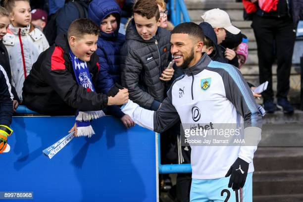 Nahki Wells of Burnley shares a joke with a young Huddersfield Town fan prior to the Premier League match between Huddersfield Town and Burnley at...