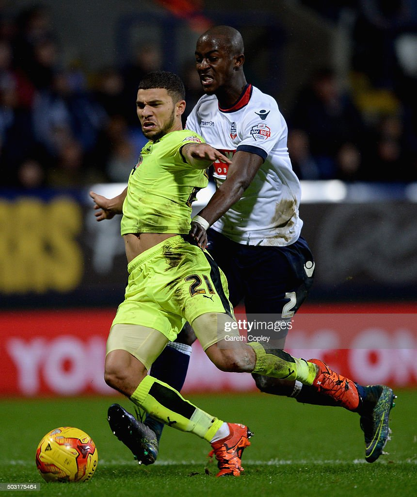 Nahki Wells of Huddersfield Town is tackled by Prince-Desir Gouano of Bolton during the Sky Bet Championship match between Bolton Wanderers and Huddersfield Town at the Macron Stadium on January 2, 2016 in Bolton, United Kingdom.