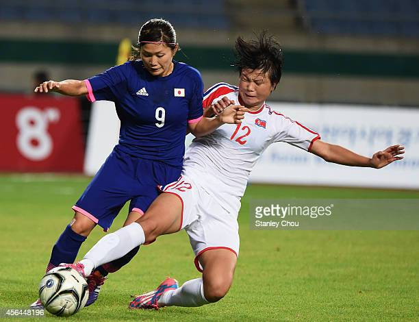Nahomi Kawasumi of Japan is tackled by Kim Yunmi of North Korea during the Football Women's Gold Medal match between North Korea and Japan during day...